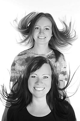 Low Key Freundefoto zwei Frauen hintereinander stehend, deren Haare nach oben wehen.