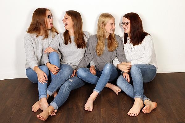Freundefoto vier sitzende Frauen in Jeans.