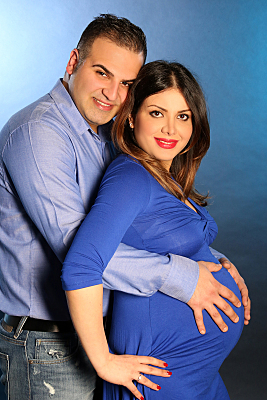 Foto Babybauch einer stehenden Schwangeren in blauem Kleid, die von hinten von ihrem Partner umarmt wird.