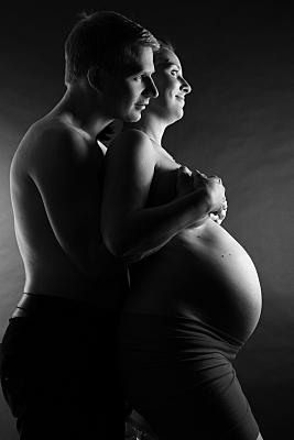 Low Key Foto Babybauch stehende, nackte Schwangere, die von hinten von ihrem Partner über der Brust umarmt wird.