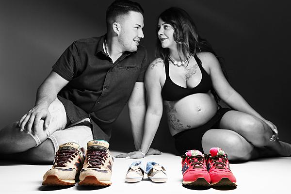 Low Key Foto Babybauch Schwangere und Partner im Hintergrund mit farbigen Turnschuhen für Erwachsene und ein Baby im Vordergrund.