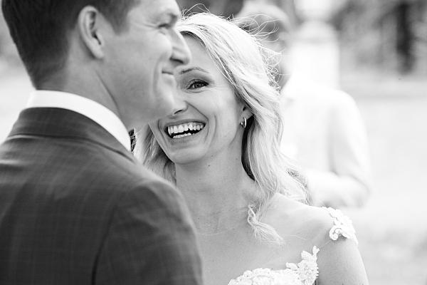 Low Key Hochzeitsfoto sich gegenüber stehendes, sich anlächelndes Brautpaar.