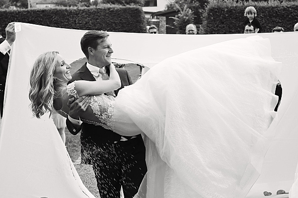 Low Key Hochzeitsfoto eines Bräutigams, der seine Braut auf Händen durch ein ausgeschnittenes Herz trägt.