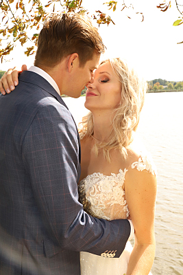 Hochzeitsfoto sich küssendes Brautpaar am See.