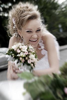 Hochzeitsfoto Braut mit Brautstrauß, die sich über ein Auto beugt.