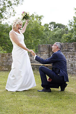 Hochzeitsfoto kniender Bräutigam vor Braut mit Brautstrauß.