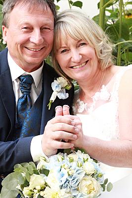Hochzeitsfoto Brautpaar, das die Eheringe auf den ausgestreckten Daumen balanciert.