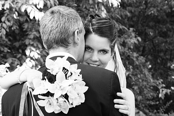 Low Key Hochzeitsfoto sich umarmendes Brautpaar mit Brautstrauß.