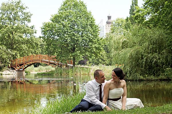 Hochzeitsfoto sitzendes Brautpaar am See mit Brücke im Hintergrund.