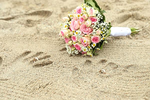 Hochzeitsfoto auf Sand liegender Hochzeitsstrauß mit Handabdrücken.