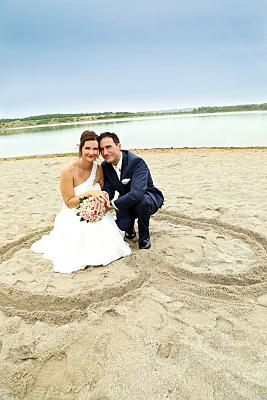 Hochzeitsfoto hockendes Brautpaar am See.