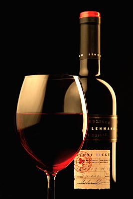 Werbefoto Rotweinflasche mit gefülltem Weinkelch im Vordergrund vor schwarzem Hintergrund.