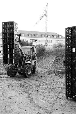 Bilddokumentation Kranwagen auf Baustelle, der mehrere Kisten hochhebt.