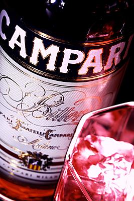 Werbefoto Campari-Flasche in Detailansicht mit gefülltem Glas mit Eiswürfeln im Vordergrund.