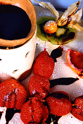 Werbefoto Schokofondue mit Schokoladen-betreufelten Erdbeeren, Kiwi und Physalis.