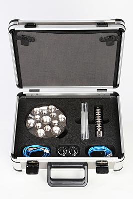 Werbefoto geöffneter, silberner Koffer mit silbernen Metallgegenständen und aufgerollten, blauen Kabeln drin.