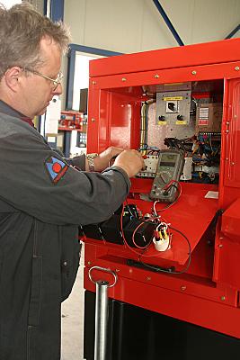 Bilddokumentation Mann in Arbeitskleidung vor einem roten Schaltkasten.