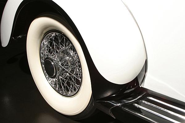 Low Key Werbefoto eines Rades mit Radkasten eines weißen Oldtimer-Wagens.