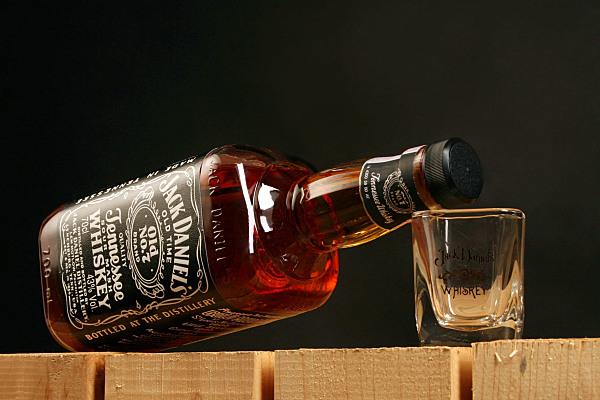 Werbefoto an ein Schnappsglas gelehnt, liegende Jack Daniels Flasche auf Holzbalken.