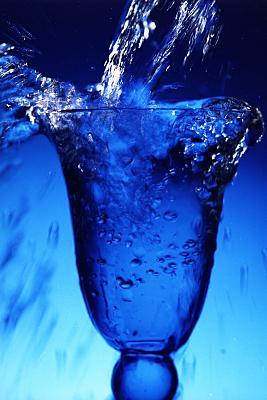 Werbefoto blauer Sektkelch mit einsprudelndem Wasser vor blauem Hintergrund.