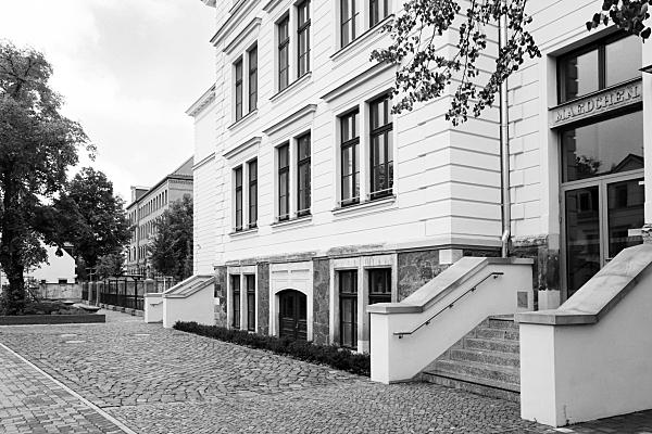 Schwarz-weiß Architekturfoto weiße Hausfassade mit breitem Treppenaufgang und gepflastertem Vorplatz.
