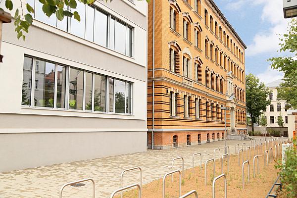 Architekturfoto weißes, modernes Haus und anschließende, gelbe Klinker-Hausfassade mit vorgelagerten Fahrradständern und Gehweg.