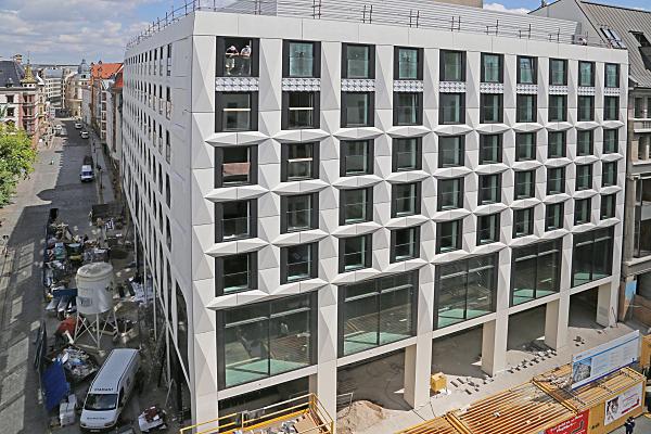 Architekturfoto Baustelle Eckgebäude mit Baufahrzeugen, Silo und an ein Fenster gelehnte Bauarbeiter.