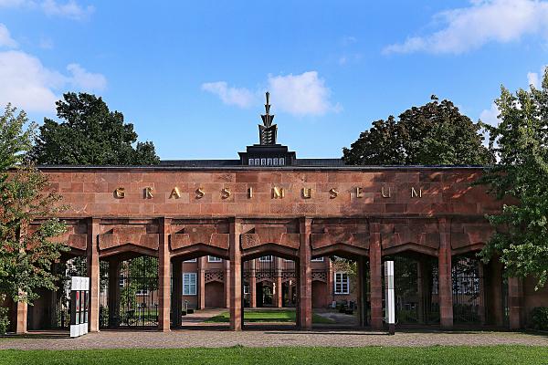 Architekturfoto Torbogen-Eingang Grassimuseum im Vordergrund mit Museumsgebäude aus rotem Sandstein im Hintergrund.