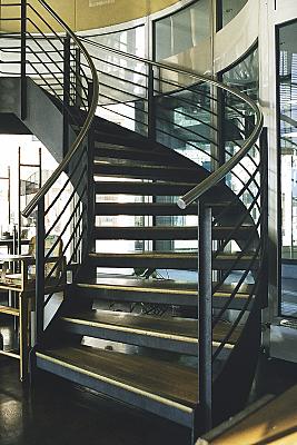 Architekturfoto gewundene Treppe mit Holzstufen und Metallrahmen vor großer Fensterfront.