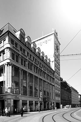 Schwarz-weiß Architekturfoto Hausfassade am Augustusplatz mit vorgelagerter Straße, Straßenbahnschienen und Passanten.