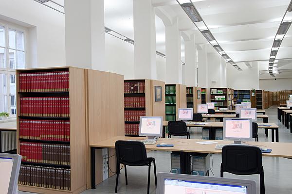 Architekturfoto heller Bibliotheksraum mit weißen Säulen, Bildschirmarbeitsplätzen und hellen Holzregalen, in denen rote Buchbände stehen.