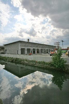 Architekturfoto Flachbau mit davor stehendem Gerüst sowie Baufahrzeugen an einem Fluss.