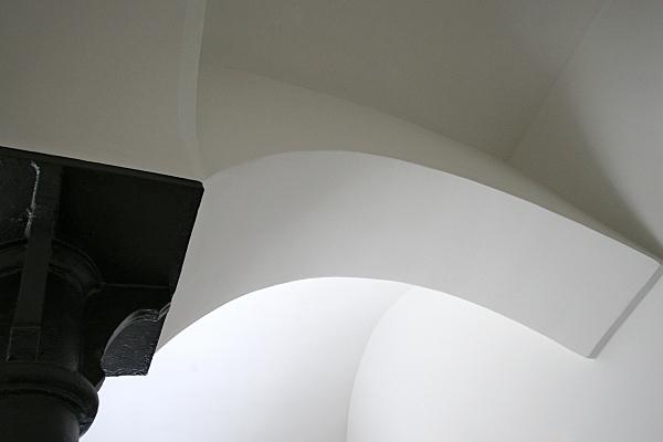 Architekturfoto weißes Kirchen-Kreuzgewölbe mit dunklem Säulenkapitell.