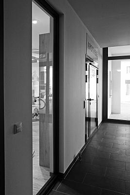 Architekturfoto Flur Büro mit offen stehender Glastür und weißer Tapete.