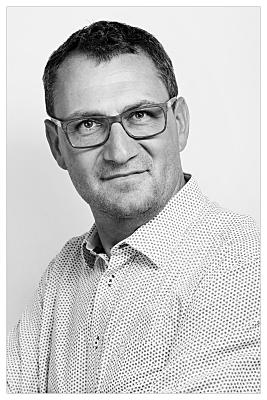 Bewerbungsfoto in schwarz-weiss von einem jungen Mann mit der Brille