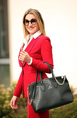 Businessfoto von einer jungen Frau mit den Brillen und mit einer Tasche in der Hand
