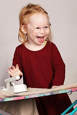Portraitfoto von einem Mädchen, die lacht beim Bügeln