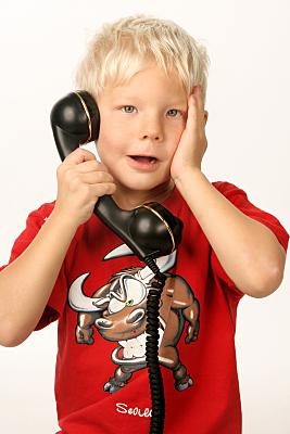 Portraitfoto von einem Kind mit einem schwarzen Telefon in der Hand