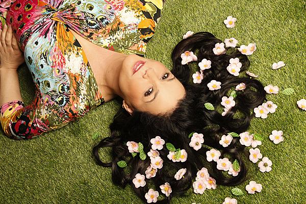 Portraitfoto von einer Frau im Liegen, auf dem Grass mit den Blumen in den Haaren