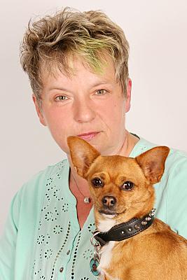 Portraitfoto von einer Frau mit einem keinen Hund, wo beide in die Kamera schauen