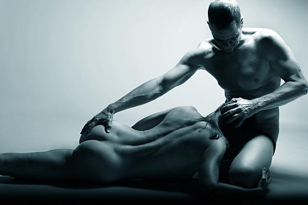 Erotikfoto schwarz-weiss von einem Pärchen, der Mann hält den Kopf von der Frau bei sich auf dem Schoß